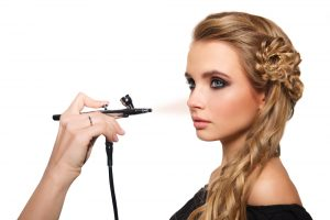 portrait of a beautiful young blonde woman on a light background. there is hand with aerograph making an airbrush make up. hair tied in a braid. copy space.
